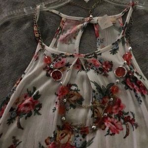 Floral tank top with attached necklace.